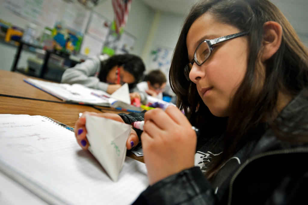 Sixth grader, Reyna Ugalde, at Foster Elementary in the Baldwin Park School District, highlights in pink the edges of her handmade polyhedron.