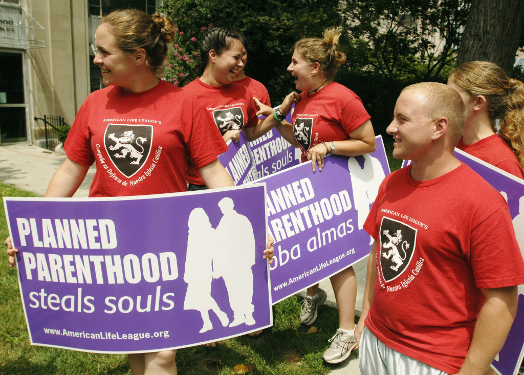 Anti-abortion activists cheers upon hearing news that they have been granted an audience with the Pope as they protest outside of a Planned Parenthood health clinic 28 July 2005 in Washington, DC. The group had walked from Maine,to Washington, DC protesting at pro-choice health clinics along the way.