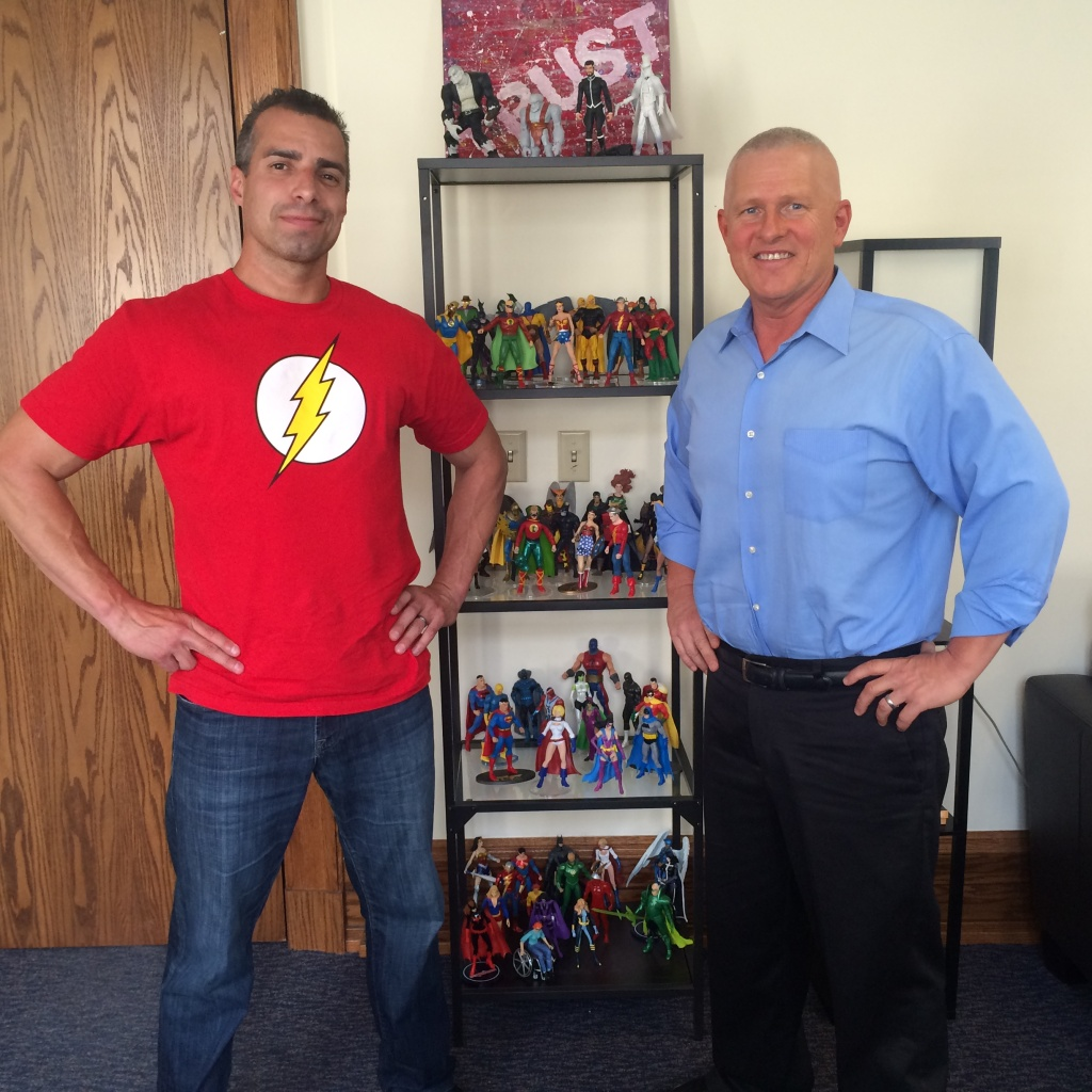 A Martinez (l) and LA City Councilman Mike Bonin pose in front of just one half of Bonin's collection of superhero action figures at his City Hall office. He apparently has even more at home.