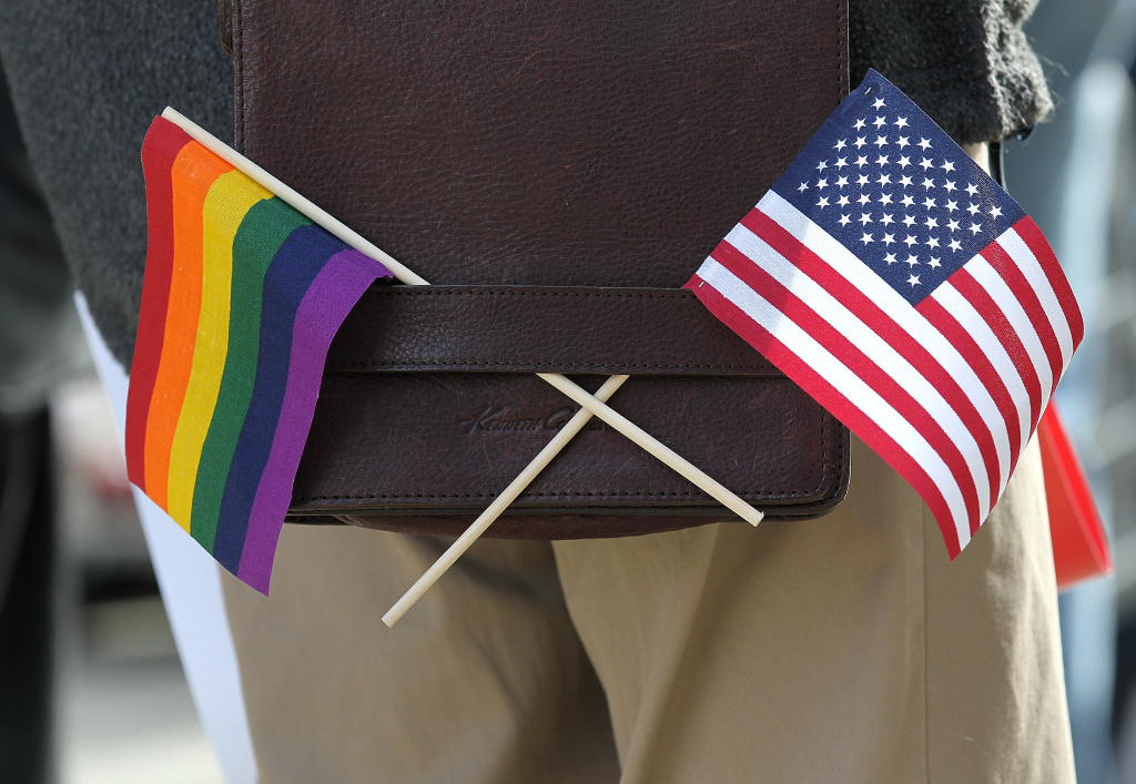 A gay pride and an American flag hang from a shoulder bag during a demonstration outside of the Phillip Burton Federal Building on June 13, 2011 in San Francisco.