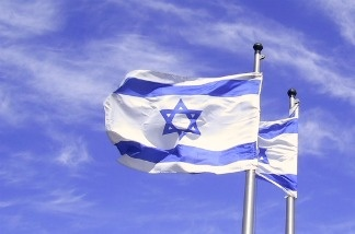An Israeli flag flies in a blue sky.