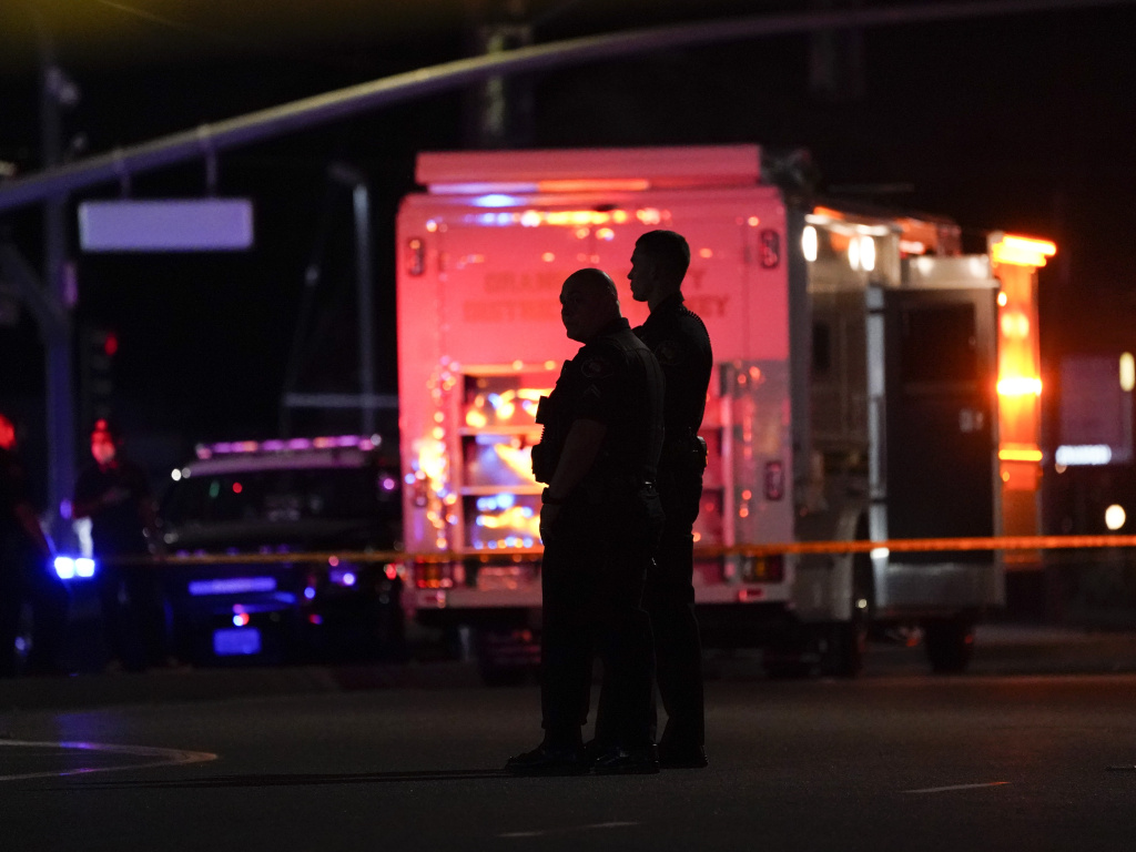 Two police officers stand outside an office building where a shooting occurred in Orange, Calif., Wednesday, March 31, 2021. The shooting killed several people, including a child, and injured another person before police shot the suspect, police said.
