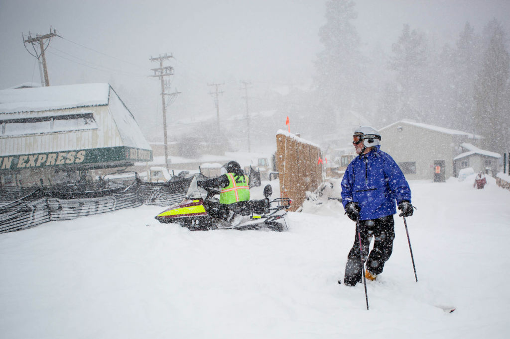 File: A skier looks back up Bear Mountain near the chair lift as a park worker makes his way toward the hill on a snowmobile.