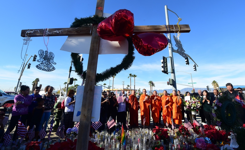 Buddhist monks from the Khmer Buddhist Society of San Bernardino join others gathered beside a makeshift shrine Dec. 7, 2015 in San Bernardino. The husband and wife behind the shooting in California that left 14 people dead December 2 were radicalized for