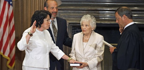 Judge Sonia Sotomayor (L), the first Hispanic justice on the us Supreme Court, is sworn in with the Judicial Oath in the East Conference room of the Supreme Court on August 8, 2009, as the 111th Justice of the US Supreme Court by Chief Justice John Roberts (R) as her mother Celina (C) holds the Bible and her brother Juan Luis (2nd L) looks on. Sotomayor is President Barack Obama's first high court nominee.
