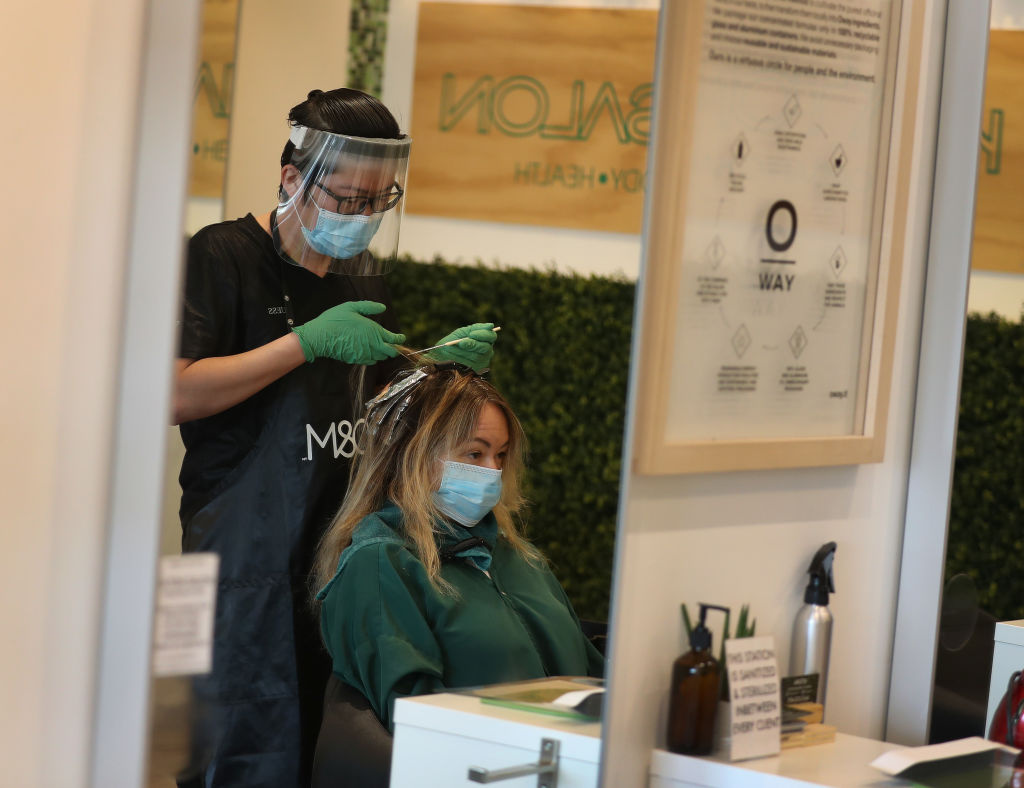Son Chau works on the hair of Christina Renbic as the Katon Salon opens on May 18, 2020 in Fort Lauderdale, Florida.