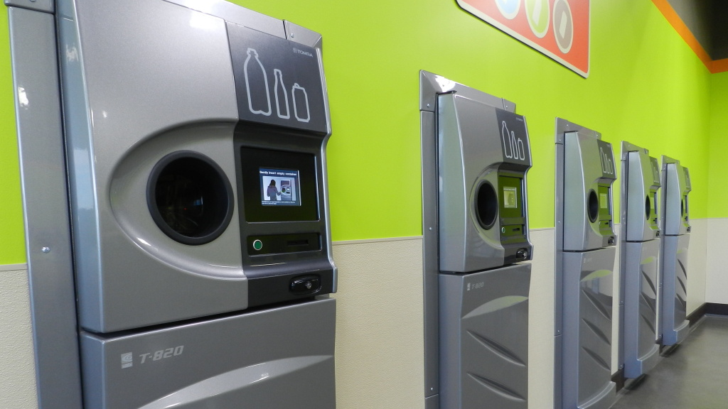 A row of brand new reverse vending machines, which collect drink containers for recycling, greets customers at the grand opening of the BottleDrop Redemption Center in Medford, Ore.