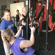Andrew Deutch, head trainer at Nerdstrong, helps someone through the ring rows.