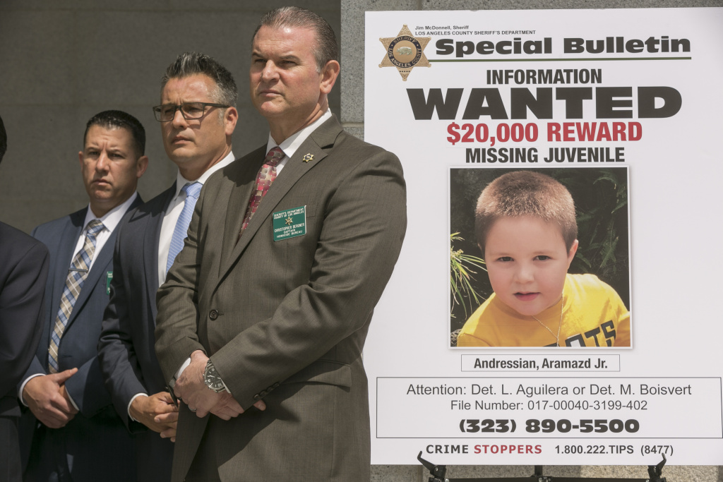 Los Angeles County Sheriff's Department Homicide Bureau Capt. Christopher Bergner, center, stands by a poster of missing 5-year-old Aramazd Andressian Jr.
