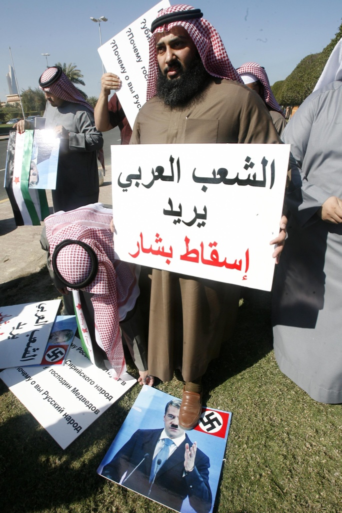 A Kuwaiti demonstrator holds a sign which reads in Arabic