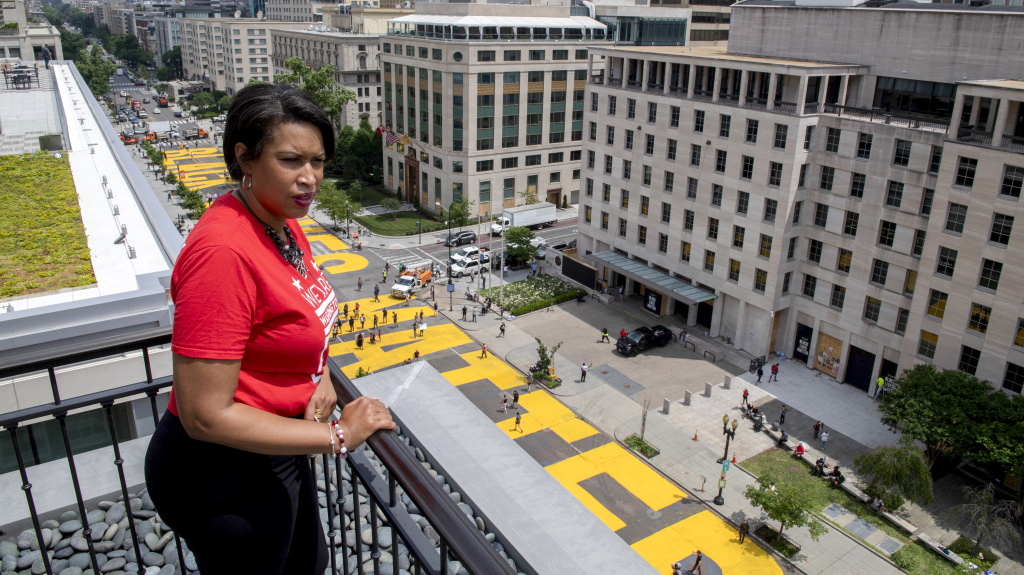 Mayor Muriel Bowser stands on the rooftop of the Hay-Adams Hotel near the White House and looks out at the words
