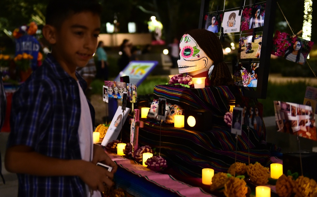 A boy views objects displayed on altars during a traditional Mexican celebration of 'Noche de Ofrenda' (Night of the Altars) in downtown Los Angeles, California on October 25, 2014, a week before the 'Day of the Dead' celebration on November 1.