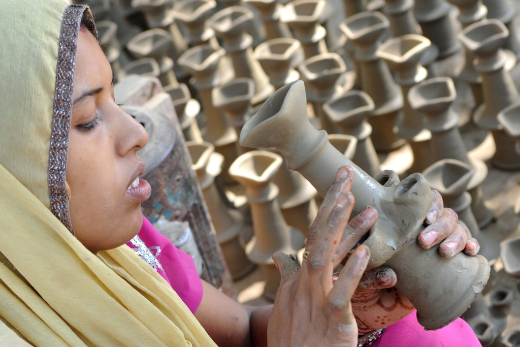 Indian craftswoman Bhawana prepares clay lamps ahead of the Hindu festival of Diwali in Amritsar on October 17, 2011.