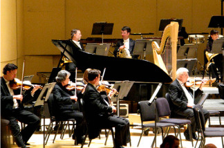 Symphony orchestra players warm up before a concert.