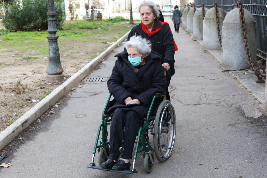 An elderly woman wearing a protective mask sitting in a wheelchair is pushed down the street.