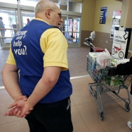 A Wal-Mart greeter speaks with a shopper who is leaving a Wal-Mart Supercenter in Bowling Green, Ohio.