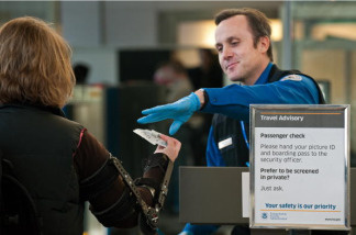An airline passenger has her boarding pass and identification papers reviewed by a TSA Officer at a security checkpoint inside Ronald Reagan Washington National Airport December 27, 2009, in Arlington, VA, near Washington, DC.