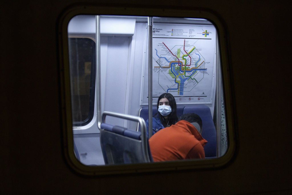 A commuter wearing a face mask rides a train stopped at the Gallery Place station in Washington, D.C.