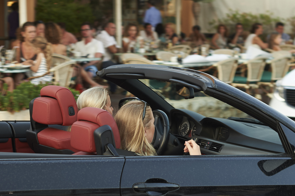 Two teenagers drive a luxury convertible car in the Portals Port on August 09, 2015.