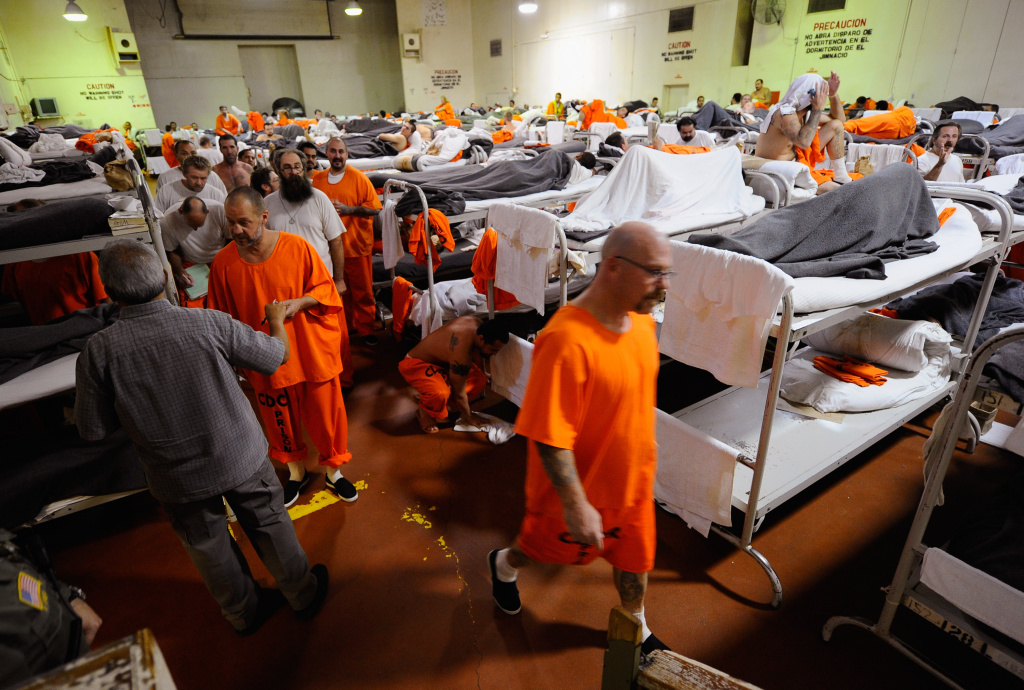 Inmates at Chino State Prison walk past their bunk beds in a gymnasium that was modified to house prisoners in this December 10, 2010 file photo taken in Chino, California. State and local authorities have since been recognized for their efforts to reduce their jail and prison populations, but officials say L.A. County still has more inmates than it should. A grant announced on Tuesday, May 26, 2015, by the MacArthur Foundation puts the county in the running for further financial assistance in alleviating its overcrowded jails.