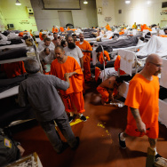 Inmates at Chino State Prison walk past their bunk beds in a gymnasium that was modified to house prisoners  in Chino, California