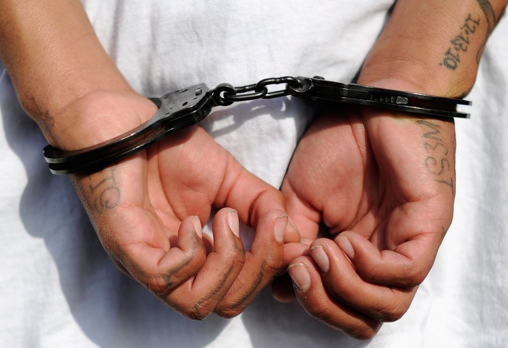 Handcuffs are seen on the hands of a twenty-year old