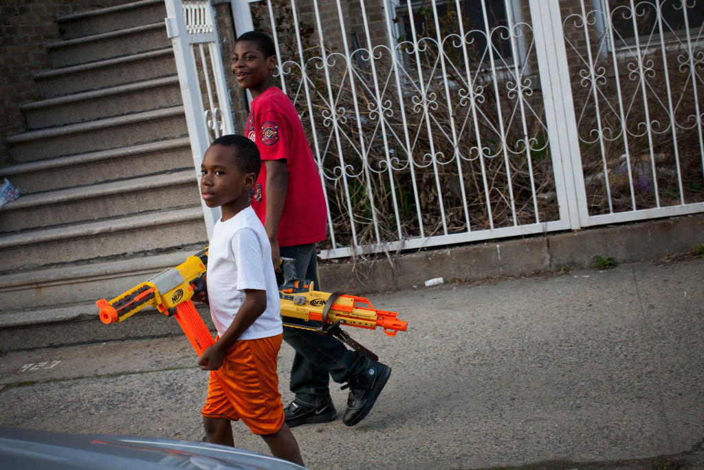 Children playing with toy guns walk in the Bronx borough New York City.