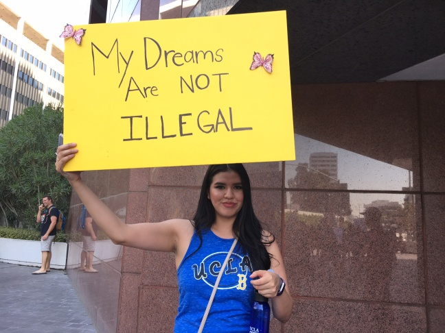 FILE: Erika Ramirez holds a sign at a  rally in downtown Los Angeles on Sept. 1, 2017 showing what she accomplished as a DACA recipient. The 31-year-old social worker credits the program for her success.