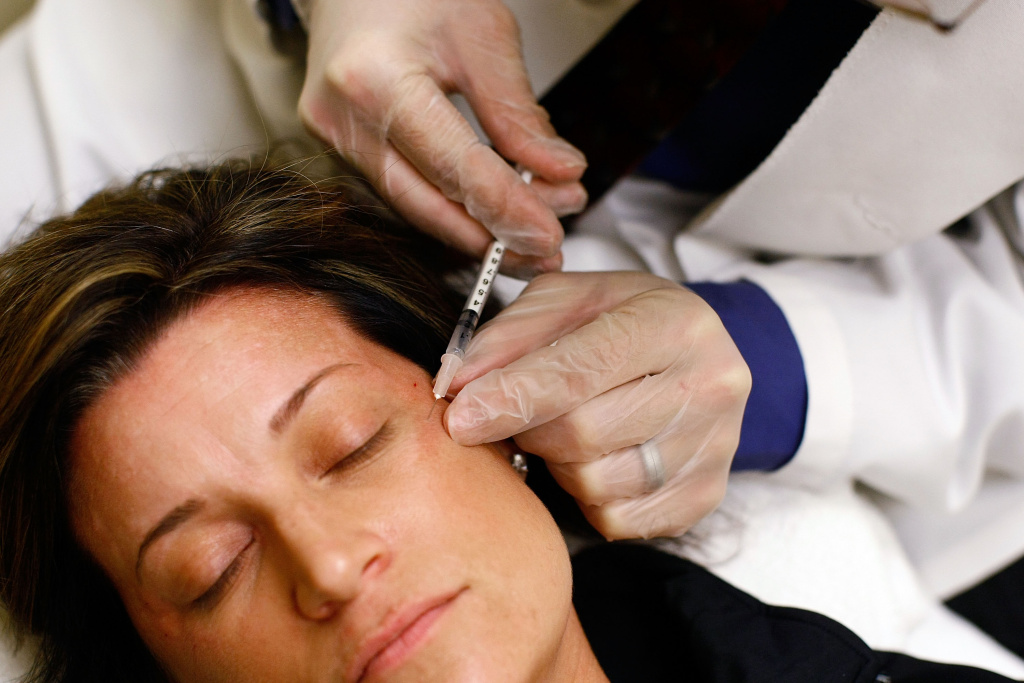 Recently laid off worker Lyn Talent receives a free Botox injection during an event called the