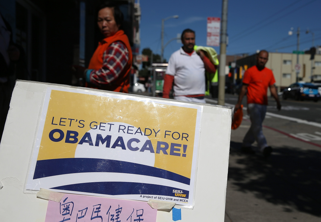 Pedestrians walk by a sign posted outside of a healthcare enrollment fair on March 18, 2014 in San Francisco, California.