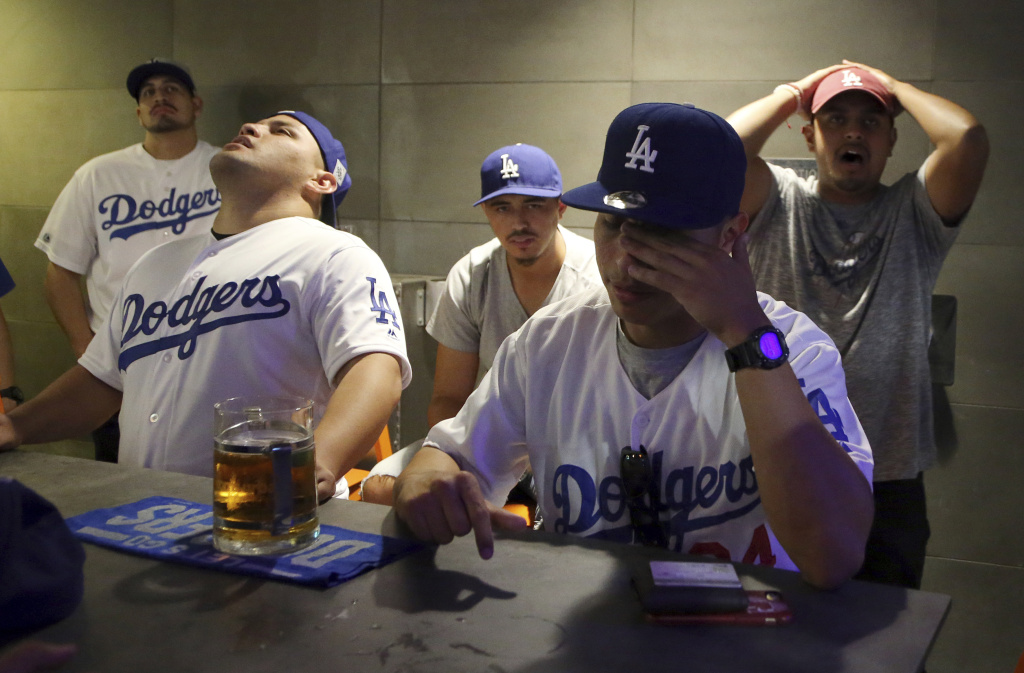 Dodger fans including, seated from left, Roberto Rosa and Gabriel Chulo, and Andy Tobias, right rear, react to their team's 5-1 loss at Tom's Urban restaurant and bar in the L.A. Live entertainment complex in downtown Los Angeles in decisive Game 7 of the World Series between the Los Angeles Dodgers and the Houston Astros, Wednesday, Nov. 1, 2017. (AP Photo/Reed Saxon)