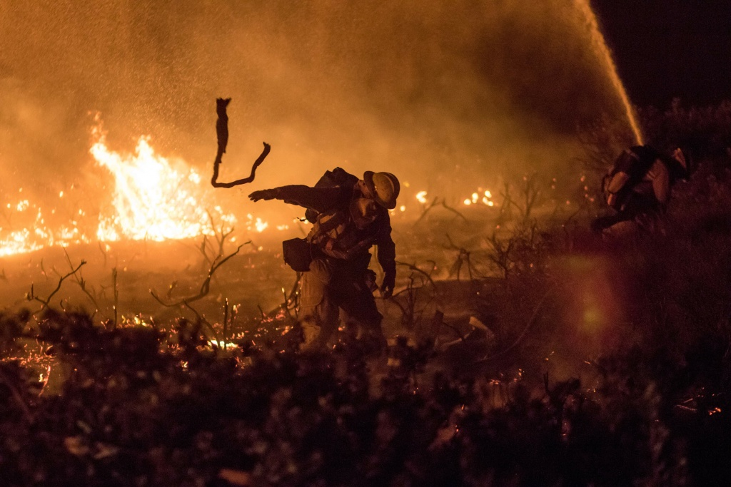A firefighter works to extinguish the Thomas Fire as it burns past the 101 Highway towards the Pacific Coast Highway in Ventura, California, Dec. 7, 2017.