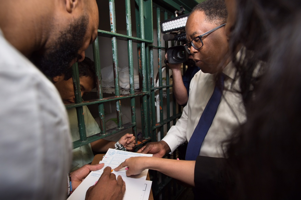 Rapper Common and Supervisor Mark Ridley-Thomas help an inmate at LA County Men's Central Jail register to vote. Photo courtesy of Bryan Chan / Los Angeles County Board of Supervisors.