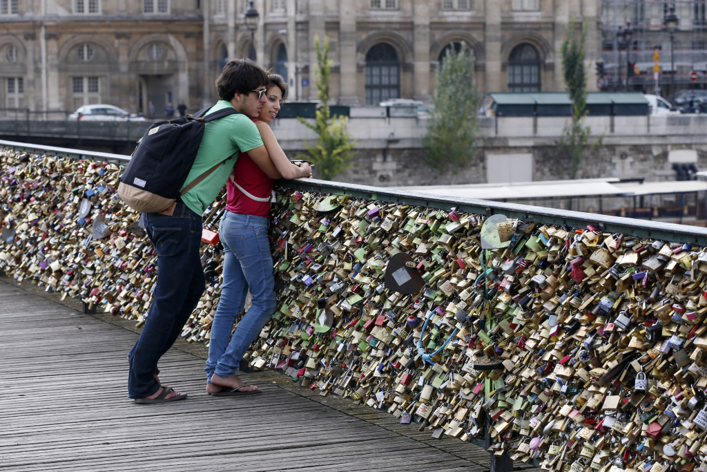 A couple is seen on the Pont des Arts where padlocks are attached to the railing, on August 30, 2013 in Paris. Due to security reason authorities consider removing the 'Love locks' that have been attached to the Pont des Arts bridge since 2008 by thousand of lovers.