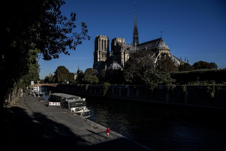 A pedestrian walks on the banks of the river Seine near the Notre-Dame de Paris cathedral in Paris on September 26, 2018.