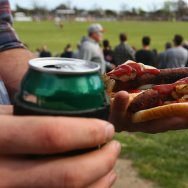 A fan is seen with a beer and barbequed sausages during the Northern Football League Grand Final match between Heidelberg and Greensborough at Preston City Oval on September 20, 2014 in Melbourne, Australia.
