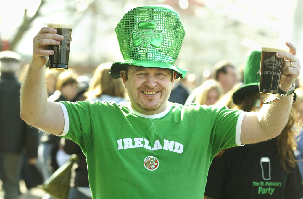 A man poses with Irish beer during St Patrick's Day celebrations March 16, 2003 in London.