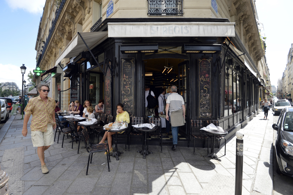 People sit at a cafe at a crossroad on the Ile Saint Louis island in central Paris in July 2013.