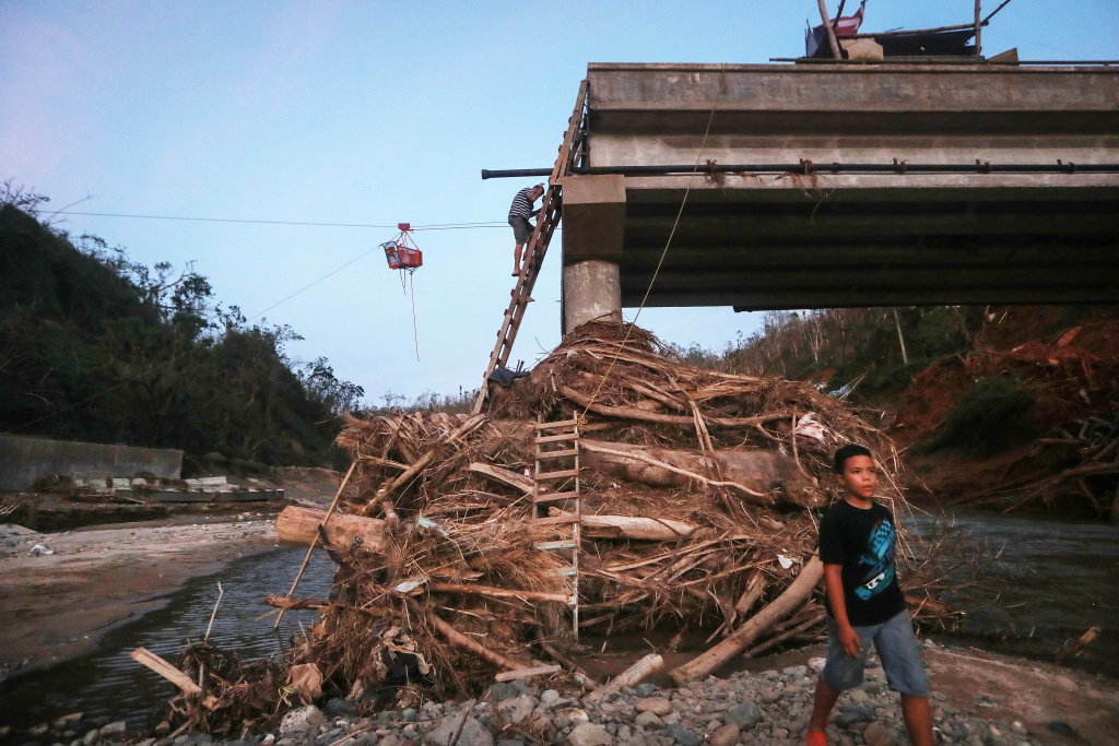 A man descends a makeshift ladder from a broken bridge spanning the Vivi River on October 20, 2017 in Utuado, Puerto Rico. The bridge was washed away during Hurricane Maria and makeshift ladders are the only way for residents of Rio Abajo to access Utuado.