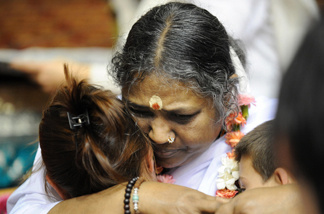 Indian spiritual leader Mata Amritanandamayi, or Amma (Mother) as she is known (C) hugs people on October 23, 2008 in Cergy-Pontoise, outside Paris during a few days trip in France. Amma, revered as a saint by her followers and a widely respected humanitarian, offers a hug to everyone who approaches her. Worldwide, Amma is said to have hugged at least 30 million people in the past 30 years.