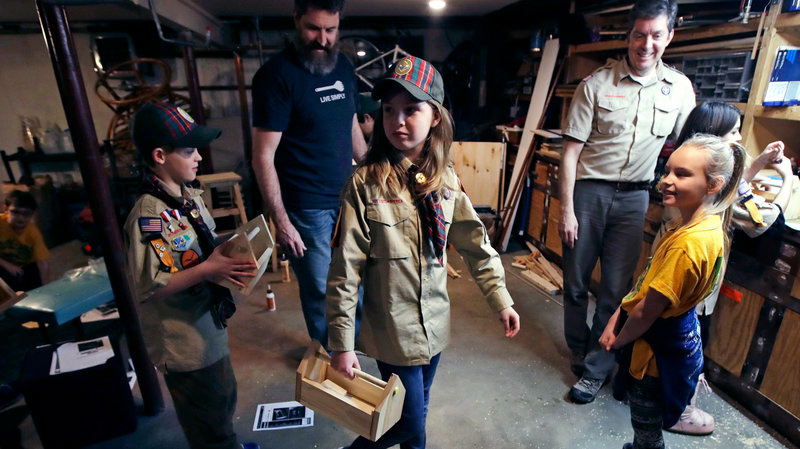 Tatum Weir, center, carries a tool box she built as her twin brother, Ian, left, follows after a Cub Scout meeting in Madbury, N.H., on March 1. For more than a century, the Boy Scouts of America's flagship program for older boys has been known as the Boy Scouts. With girls soon entering the ranks, the name will change to