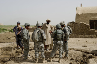 US soldiers from 1st Platoon Bravo Troop of 1st Squadron, 71st Cavalry talk with villagers during a patrol in Dand district of Kandahar Province in Afghanistan on July 24, 2010.