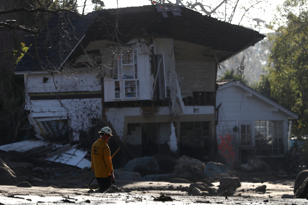 MONTECITO, CA - JANUARY 11:  An urban search and rescue team member walks by a home that was destroyed by a mudslide on January 11, 2018 in Montecito, California. 17 people have died and hundreds hundreds of homes have been destroyed or damaged after massive mudslides crashed through Montecito, California early Tuesday morning.  (Photo by Justin Sullivan/Getty Images)