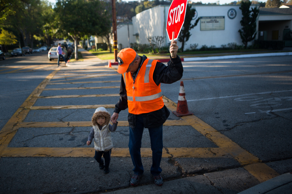 Crossing guard Tony Abdalla walks a young child across the street outside of the Arroyo Vista Elementary School in South Pasadena.
