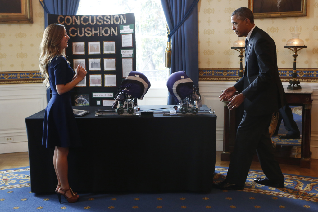 U.S. President Barack Obama looks at the Concussion cushion football helmet project from Maria Hanes, Santa Cruz, CA,, during the  2014 White House Science Fair at the White House May 27, 2014 in Washington DC. The fair celebrates the winners of STEM (science, technology, engineering and math) competitions across the country.