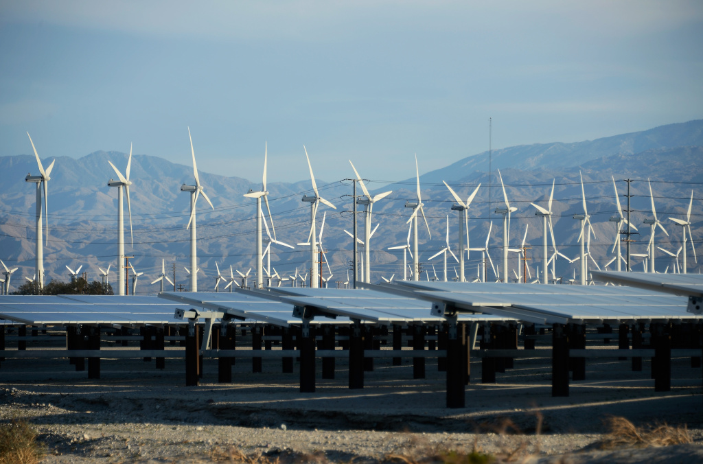 Giant wind turbines are powered by strong winds in front of solar panels on March 27, 2013 in Palm Springs, California.