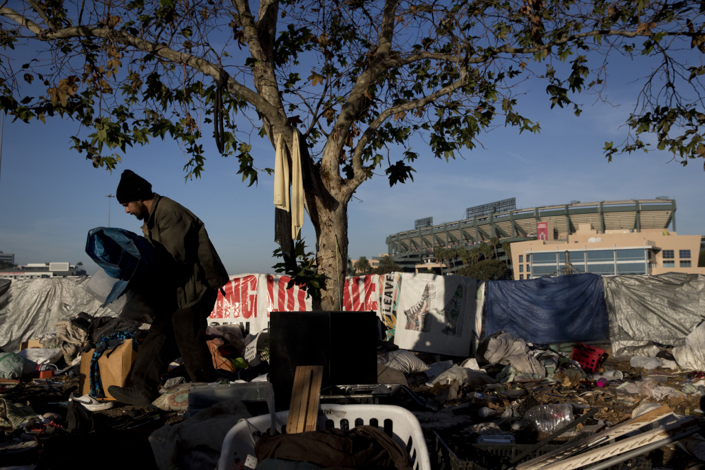 Homeless Junior Sanchez, 29, carries a tarp he found in a pile of trash in a homeless encampment on the Santa Ana River trail near Angel Stadium Saturday, Dec. 2, 2017, in Anaheim, Calif.
