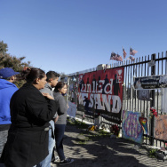 A year after the attack, people stand by a makeshift memorial for county workers near the Inland Regional Center in San Bernardino, Calif., on Friday, Dec. 2, 2016.