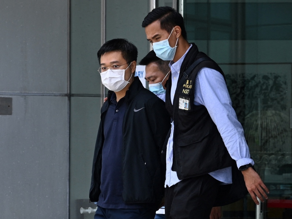 Apple Daily editor-in-chief Ryan Law is escorted by police to a waiting vehicle outside the entrance of the Apple Daily newspaper offices in Hong Kong on Thursday.