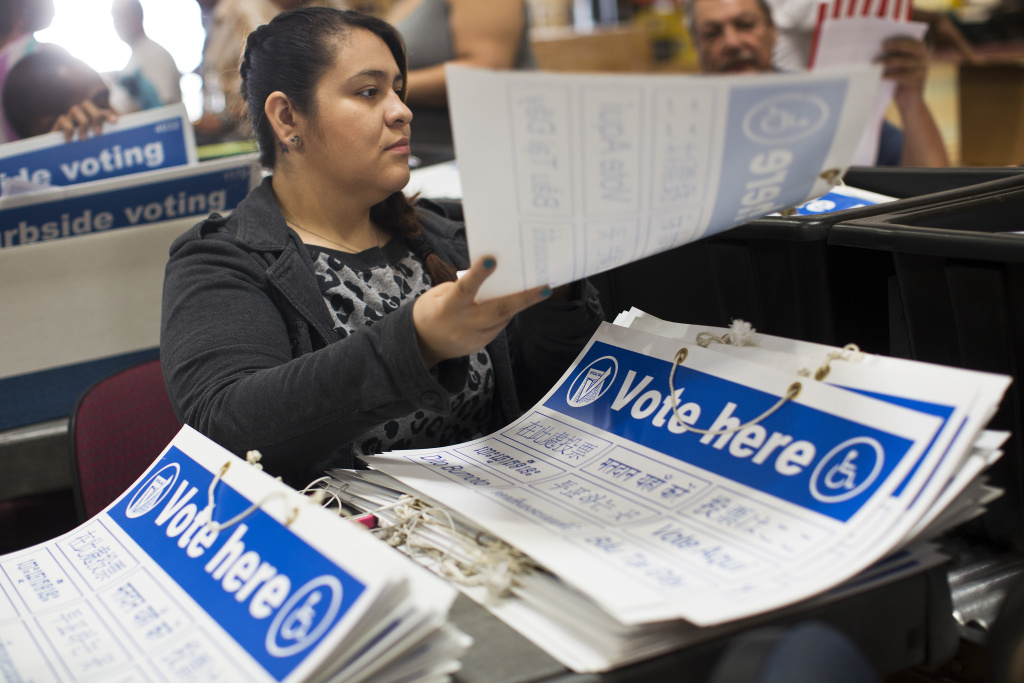 FILE PHOTO: Joana Briones places signs into supply tubs on Thursday, Oct. 23, 2014 at Los Angeles County's Elections Operations Center in Santa Fe Springs.